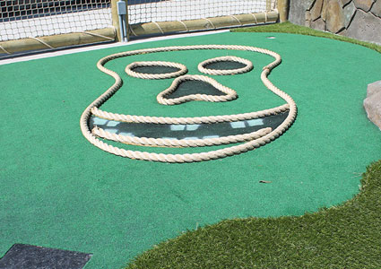 flat pirate skull outline made of rope on Putt Putt course green