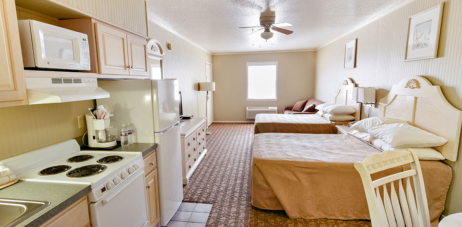 Room with two beds and kitchenette
